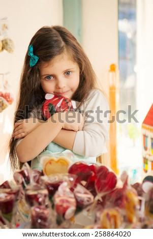 Greed  little girl with blue eyes holding lollipop in hands - stock photo