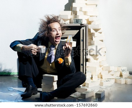 Greedy banker eats a wad of money - stock photo