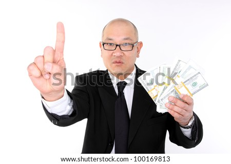 Greedy corporate executive making hand gesture with bundles of cash.