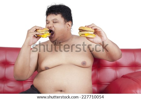 Greedy fat man eating hamburger while watching tv at home