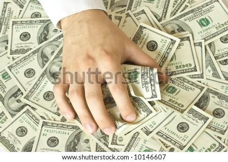 Greedy hand grabs lot of dollars - stock photo
