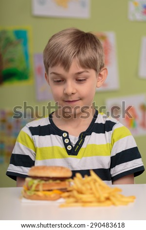 Greedy little child and fastfood for lunch - stock photo