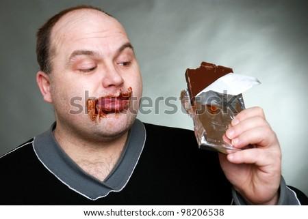 greedy man eats a chocolate bar - stock photo
