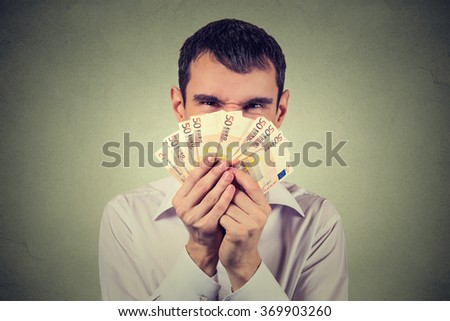 Greedy man with euro banknotes bills isolated on gray wall background   - stock photo