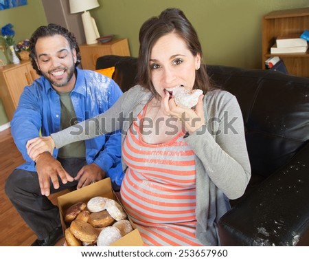 Greedy pregnant woman with hungry partner on sofa - stock photo