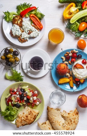 Greek appetizers  - fritters of zucchini with tzatziki sauce, Greek salad, yogurt with fresh fruit and nuts, olives, vegetables and herbs, top view.