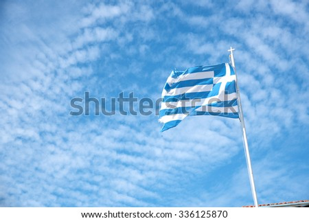 Greek blue  and  white flag waving against a blue dramatic cloudy sky - stock photo