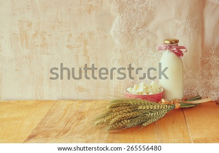greek cheese  and milk on wooden table over wooden textured background. Symbols of jewish holiday - Shavuot - stock photo