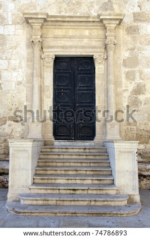 greek classical style door with steps and columns at Siracusa cathedral in Sicily Italy