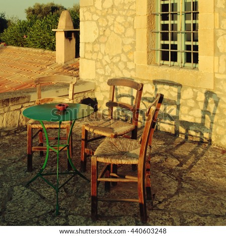 greek country outdoor restaurant on roof terrace, Crete, Greece. Square vintage toned image - stock photo