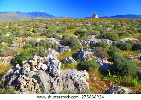 Greek countryside with limestone hills and distant wind mill in springtime, Greece  - stock photo