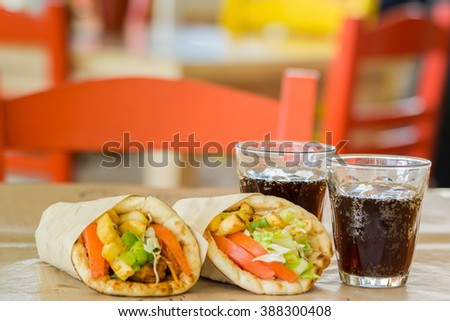 Greek cuisine, souvlaki, gyro pita. and a glass of drink. In the tavern in Greece - stock photo