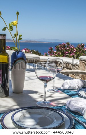Greek Dining Scene A view of the Aegean sea in the background. Outdoor table setting on Greek island of Mykonos.
