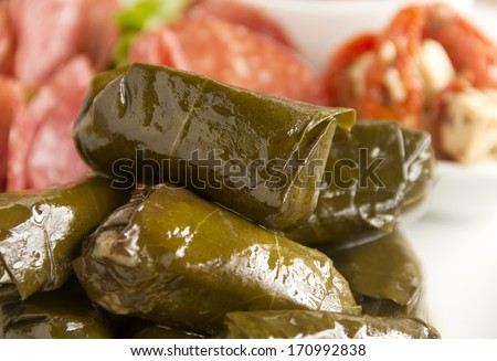 Greek dolmades wrapped with vine leaves feature in a mezze platter. - stock photo