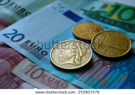 Greek drachma coins on Euro banknotes. Greek epic poet Homer depicted in the old Greek coin - stock photo