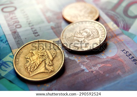 Greek drachma coins on Euro banknotes. Selective focus.Greek epic poet Homer depicted in the old Greek coin - stock photo