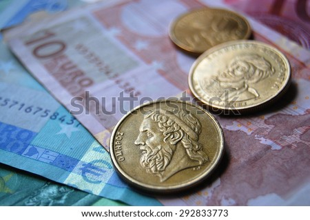 Greek drachma coins on Euro banknotes. Selective focus. Greek epic poet Homer depicted in the old Greek coin