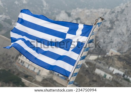 Greek flag in the wind with background of desolate landscape - stock photo