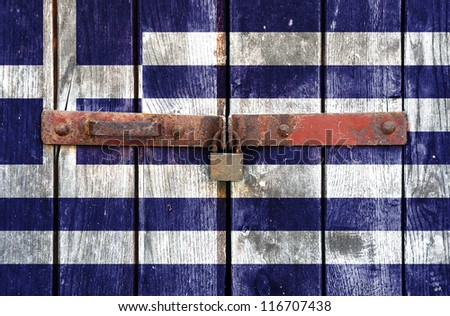 Greek flag on the background of old locked doors - stock photo