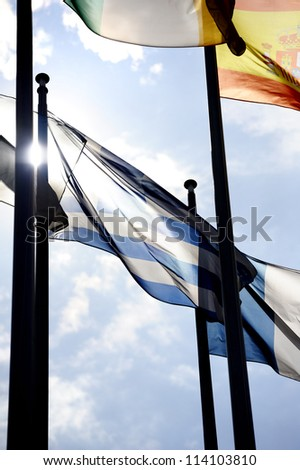 Greek flag waving between flags of Spain Italy and France in front of European Parliament (Brussels) while Eurozone is facing a financial crisis. Contre-jour technique used to emphasize the Greek flag