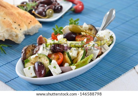 Greek fried vegetables with feta cheese, olives and pita bread - stock photo