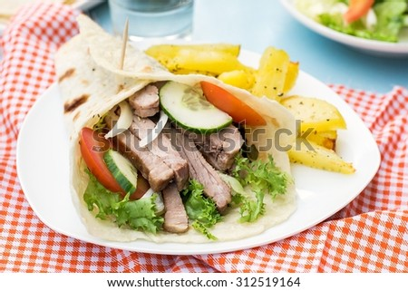 Greek gyros with pork, vegetables, potatoes and homemade pita bread. Selective focus - stock photo