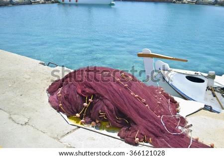 greek island fishing nets and a boat - stock photo