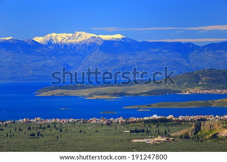 Greek landscape with snowy mountains across blue waters of the Gulf of Corinth, Greece - stock photo