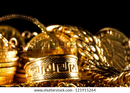 Greek meander ring Jewels and gold coins over dark background - stock photo