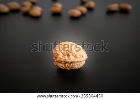 Greek nut close isolated on black background with the smaller nuts in the far background - stock photo