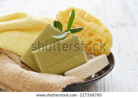 "Greek olive soap with bath towels and bath sponge in bowl closeup. The words on soap translates as ""best quality"" - stock photo"
