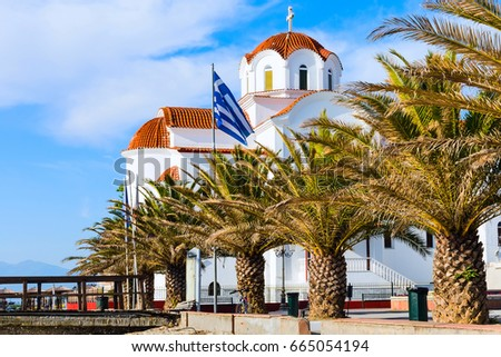 Greek orthodox Church in Paralia Katerini, wooden pier, palm trees and sandy beach, Greece