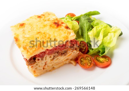 Greek pastitsio pasta topped with minced beef, tomatoes, bechamel sausce and cheese, served with a salad.