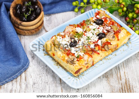 Greek pizza. Greek Pizza with chicken, feta and olives with mixed cherry tomato salad. Shallow DoF - stock photo