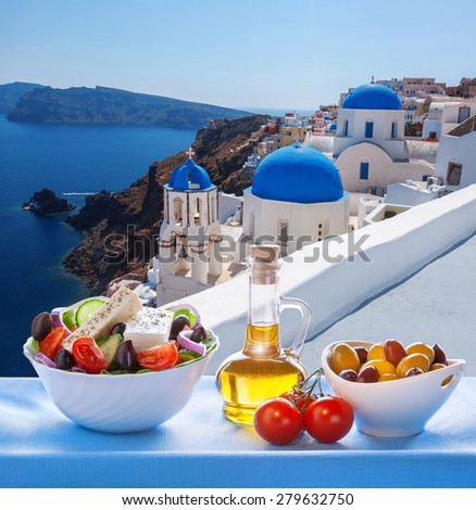 Greek salad against church in Oia village, Santorini island in Greece - stock photo