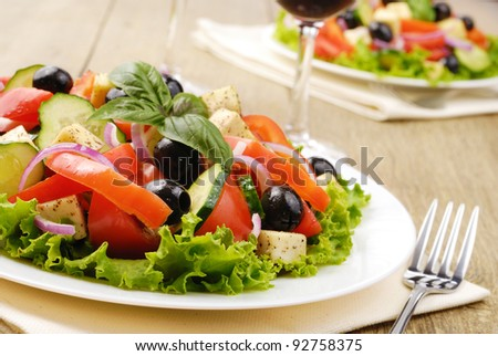 Greek salad and glass of red wine on the oak table - stock photo