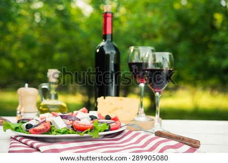 Greek salad and glass of wine on white wood table outdoors green background - stock photo