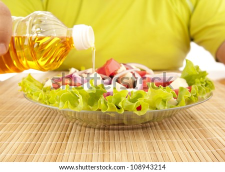 Greek salad and pouring olive oil, Greek cuisine - stock photo