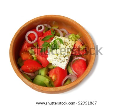 Greek salad in a clay plate isolated on a white background