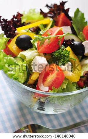 Greek salad in glass bowl on wooden background closeup