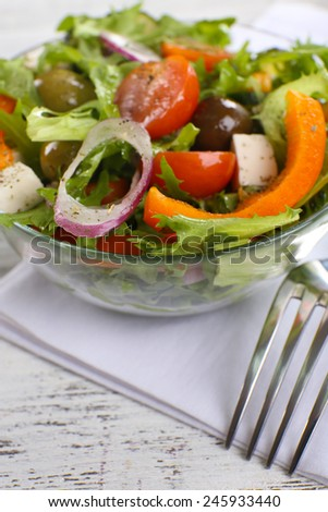 Greek salad in glass dish on napkin and color wooden background - stock photo