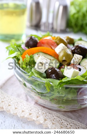 Greek salad in glass dish on napkin and wooden table background - stock photo