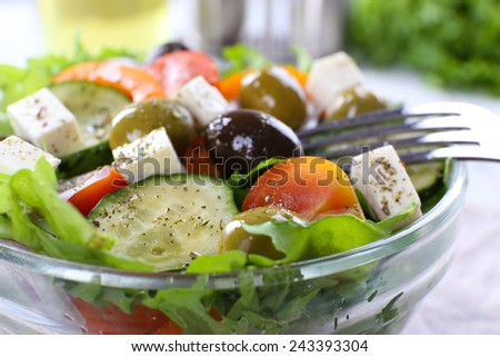 Greek salad in glass dish with fork, closeup - stock photo