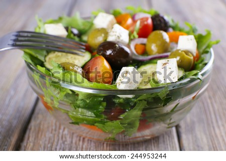 Greek salad in glass dish with fork on wooden background - stock photo