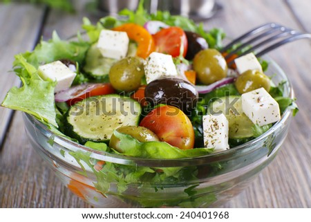 Greek salad in glass dish with fork on wooden table background - stock photo