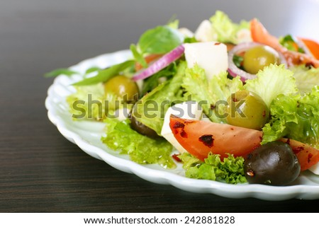 Greek salad in plate on wooden table background - stock photo
