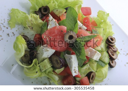greek salad isolated with tomatoes,lettuce,feta cheese,green pepper and beads of olive.