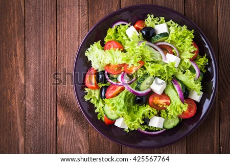 Greek salad (lettuce, tomatoes, feta cheese, cucumbers, black olives, purple onion) on dark wooden background top view. Healthy food. Space for text. - stock photo