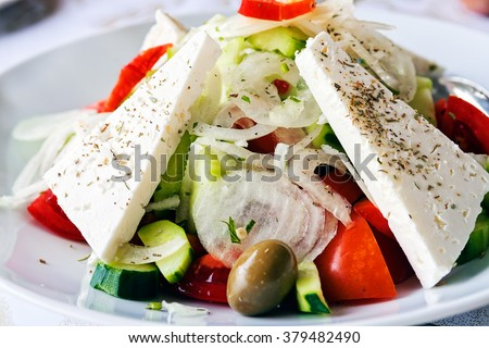 Greek salad on a plate at small restaurant on Mediterranean seaside - stock photo