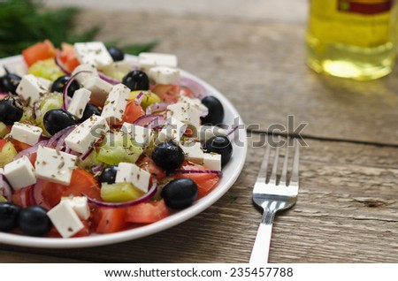 Greek salad on a plate with dill and olive oil - stock photo